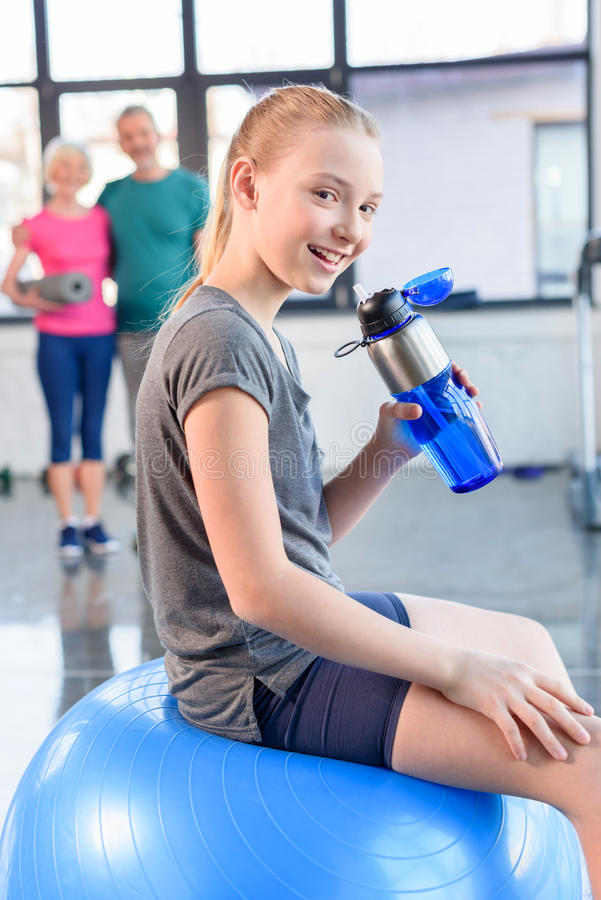 Couple looking at smiling girl training on fitness ball and drinking water in gym stock images