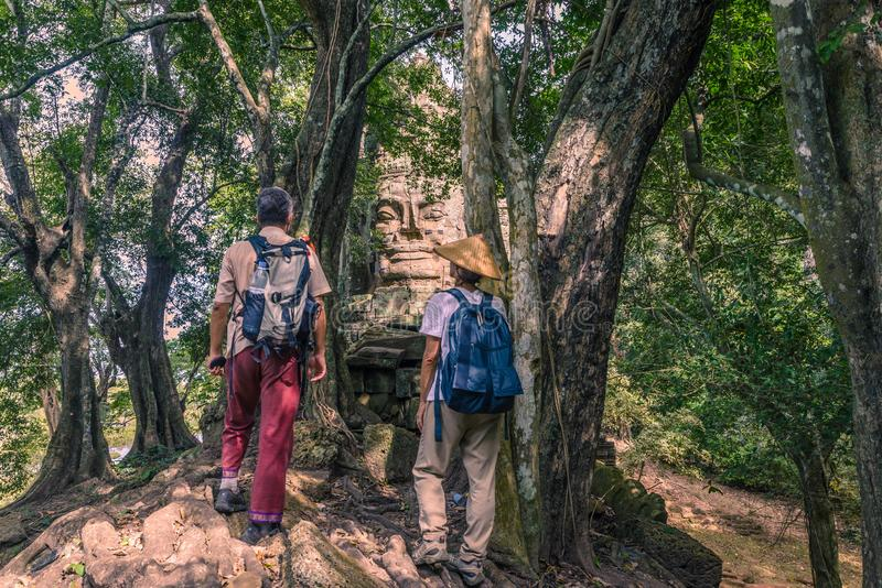 Couple looking at stone faces in the jungle, Bayon Temple Angkor Thom. Buddhism meditation concept, world famous travel royalty free stock photography
