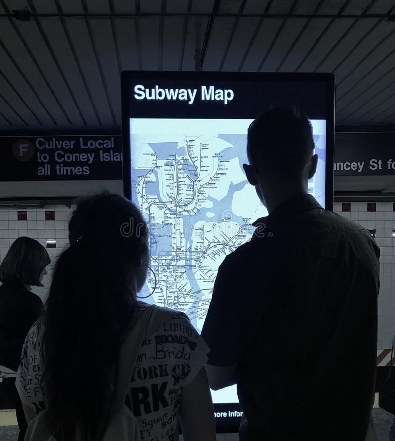 Couple Looking at Subway Information Digital Screen for Directions on NYC Subway Map MTA Train Station royalty free stock photo