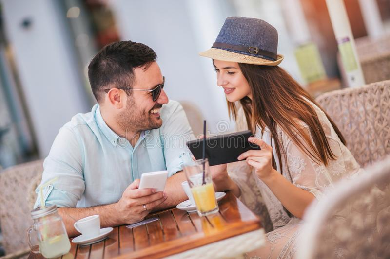 Couple looking at a tablet at the cafe terrace. Cute couple looking at a tablet at the cafe terrace stock photography