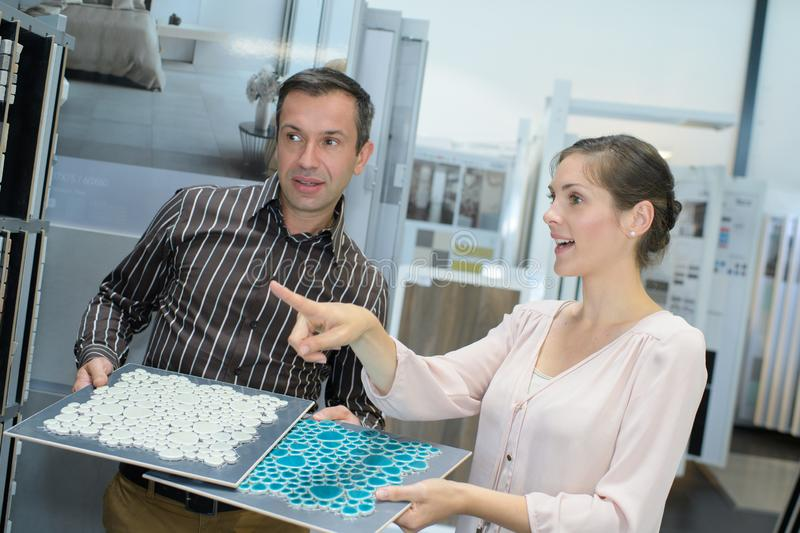 Couple looking at tile samples stock photography