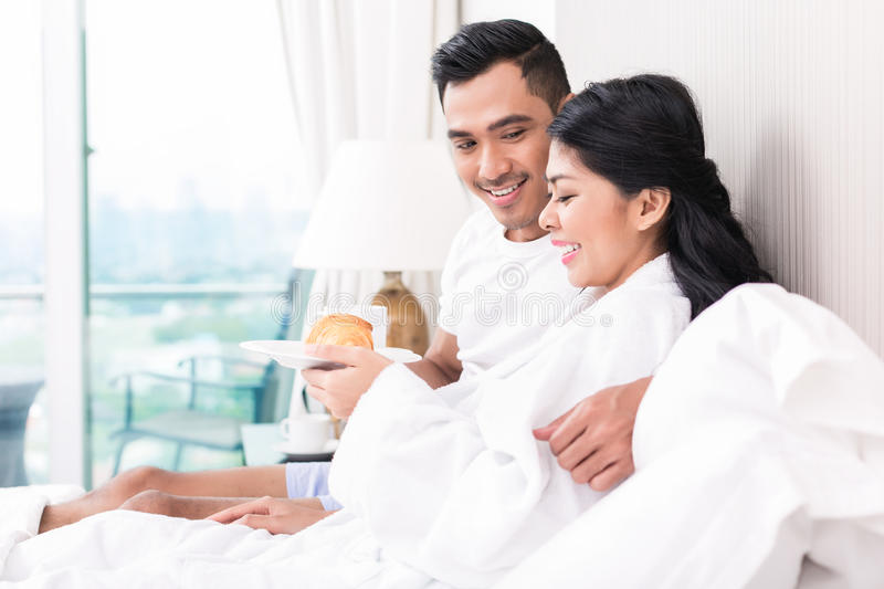 Couple lounging in bed at morning. Asian couple lounging in bed at morning stock photos
