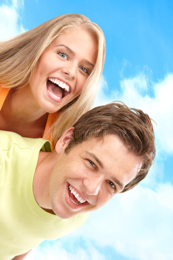 Couple in love. Young love couple smiling under blue sky royalty free stock image