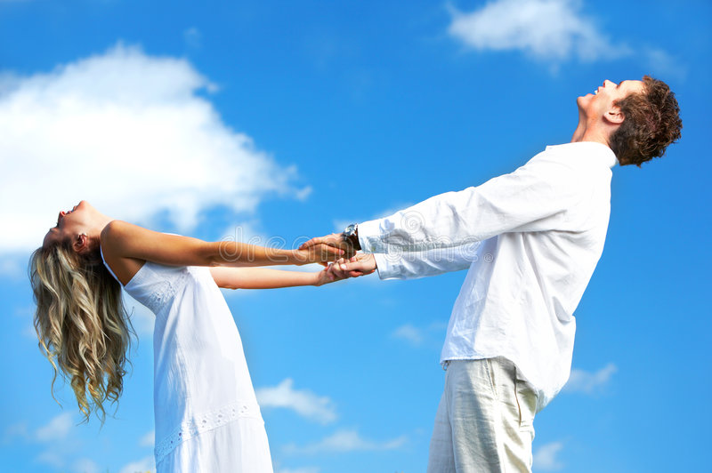 Couple in love. Young love couple smiling under blue sky royalty free stock images