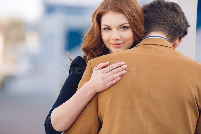 Couple in love on the background of the spring city. Happy couple in love,a men with dark hair in a light brown jacket and white striped shirt and a beautiful stock image
