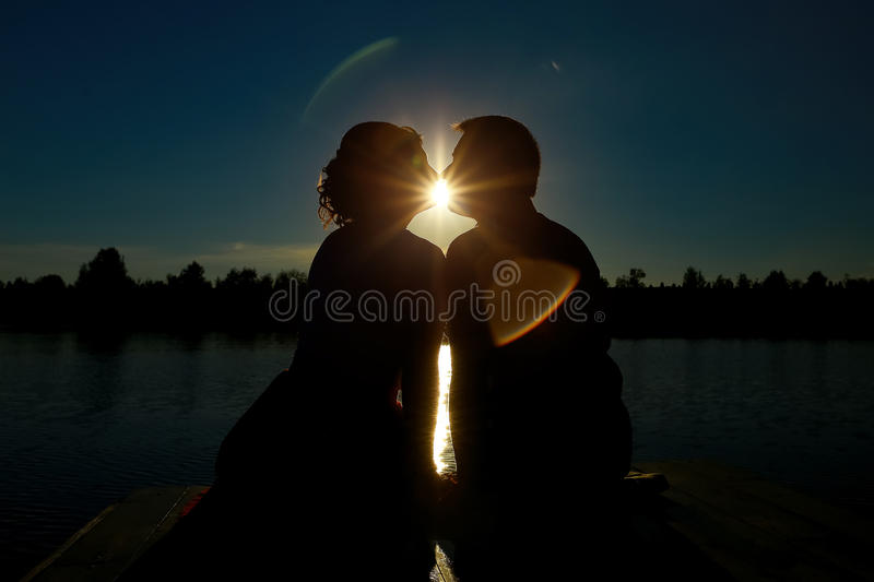 Couple in love backlight silhouette at lake. Silhouette of couple kissing at sunset royalty free stock photo