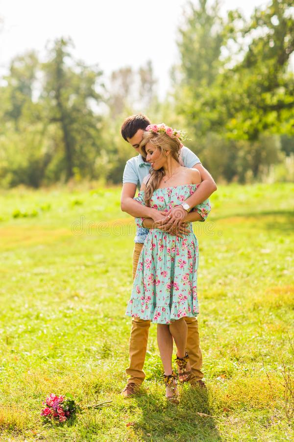 A couple in love beautiful young men hugging in a summer park on a sunny day stock photography