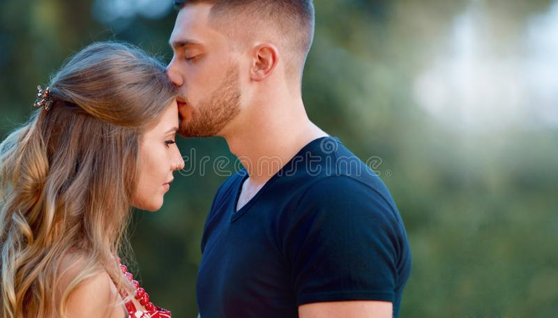 A couple in love beautiful young men kissing in a summer park on a sunny day royalty free stock photo