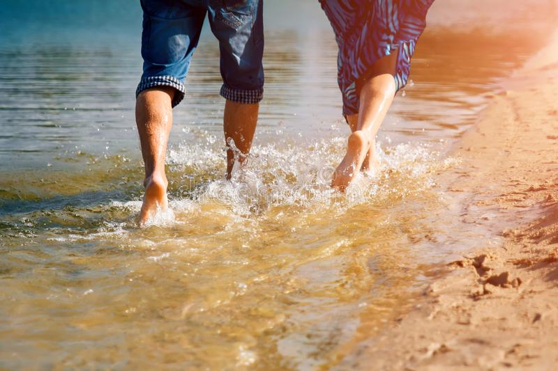 A couple in love with a bee-hose run along the water, beach sand stock photography