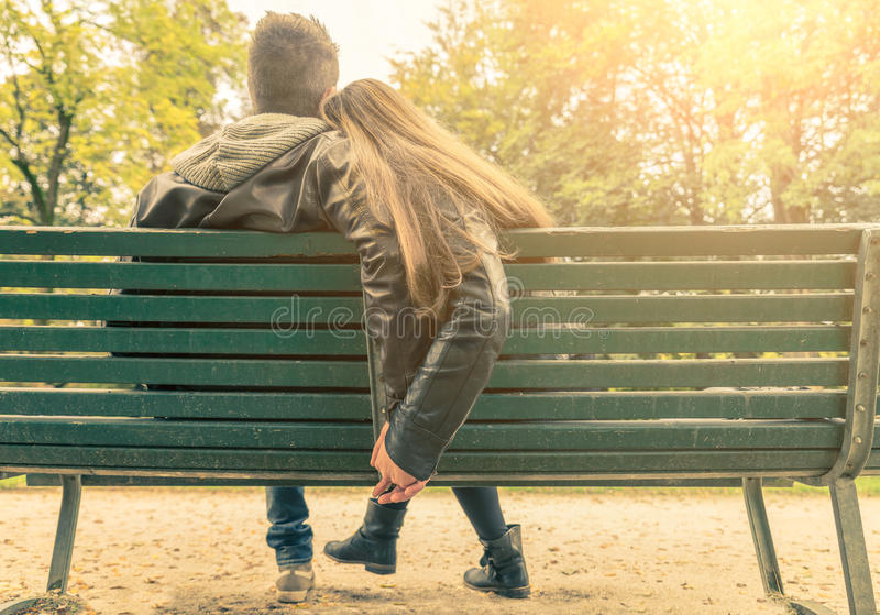 Couple in love on a bench. Couple on a bench - Two lovers sitting on a bench in a park and holding themselves by hands - Concepts of autumn, love, togetherness stock images