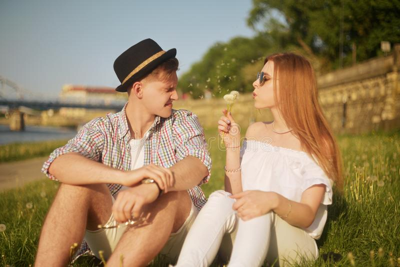 Couple in love blowing blowballs flowers in faces of each other. Smiling and laughing people having good time outside. On summer warm day. Allergy to flowering royalty free stock photo