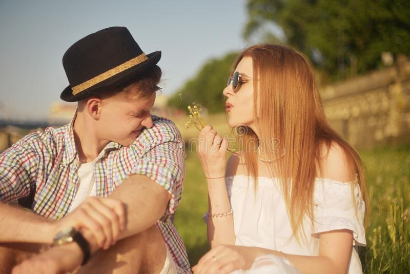 Couple in love blowing blowballs flowers in faces of each other. Smiling and laughing people having good time outside. On summer warm day. Allergy to flowering stock images