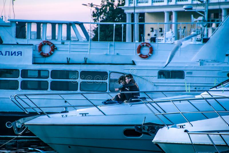 Couple in love on the bow of the yacht. Yachts in the seaport of Sochi. Evening Sochi. the reflection in the water. a great saver. Beautiful sunset royalty free stock image
