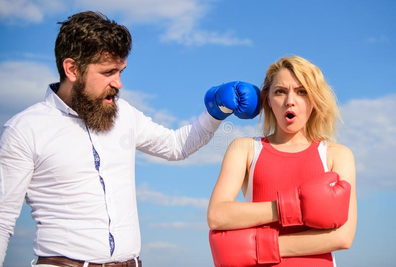 Couple in love boxing gloves sky background. Man punch girl boxing glove. She did not expect be attacked. Prepare for stock photography