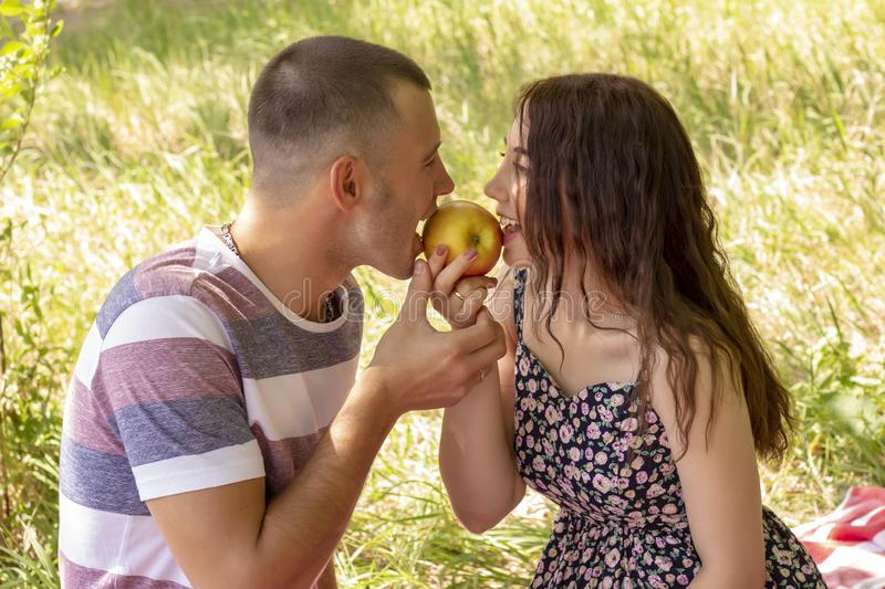 Couple in love boy and girl eat apple summer picnic Outdoors stock image