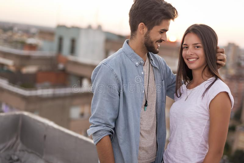 Couple in love on a building rooftop at sunset royalty free stock image