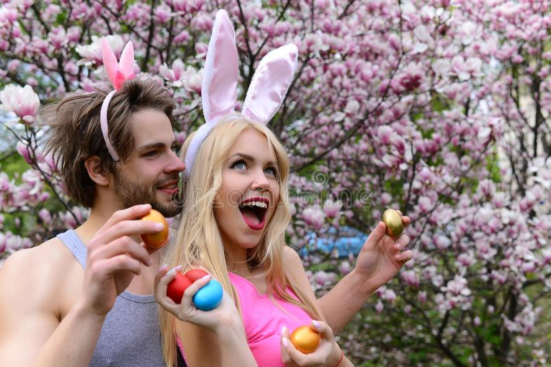 Couple in love with bunny ears holding colorful eggs royalty free stock image
