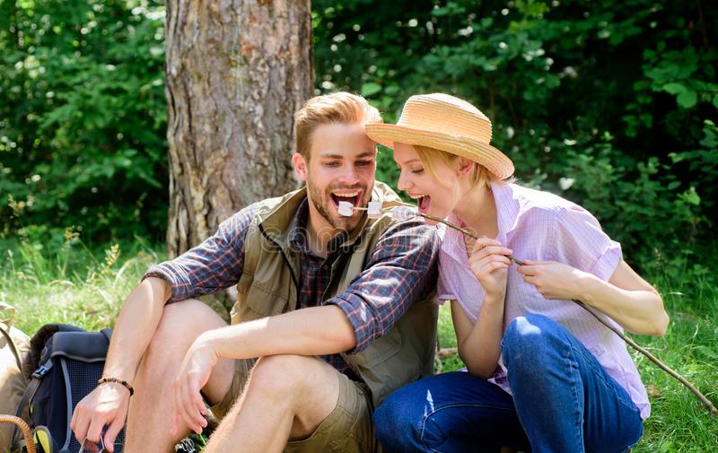 Couple in love camping forest eating roasted marshmallows. Roasting marshmallows popular group activity around bonfire royalty free stock photography