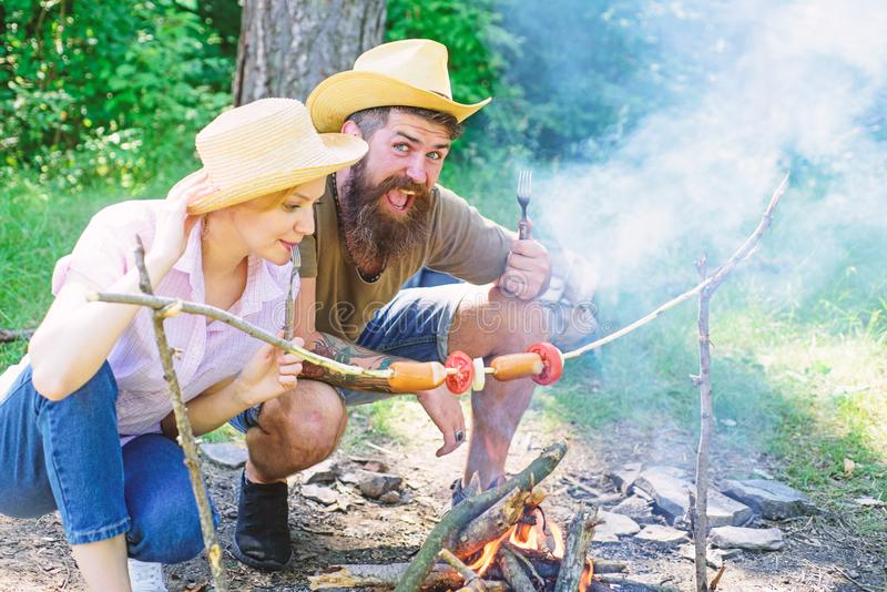 Couple in love camping forest roasting sausage at bonfire. Couple hungry tourists roasting sausages on sticks nature. Background. Traditional roasted food as royalty free stock images
