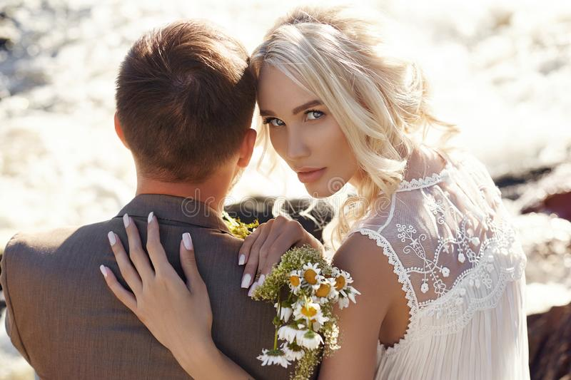 Couple in love close-up sitting on a stone on a beautiful Sunny day at sunset. Love emotions and hugs in the sun. Blonde woman royalty free stock photos
