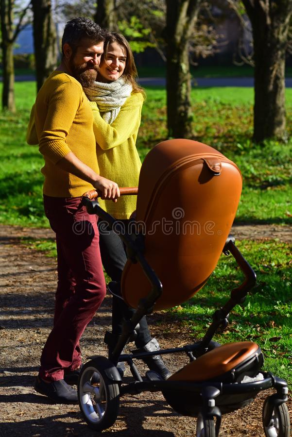 Couple in love concept. Couple in love walk with baby stroller in spring park. Two halves of the same soul.  stock images
