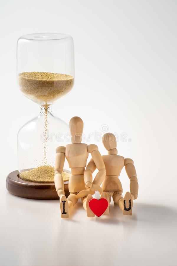 Couple love concept of I love you. Miniature wooden mannequin couple holding each other with red heart shape between I and U letters ,sand glass or hourglass on royalty free stock photo
