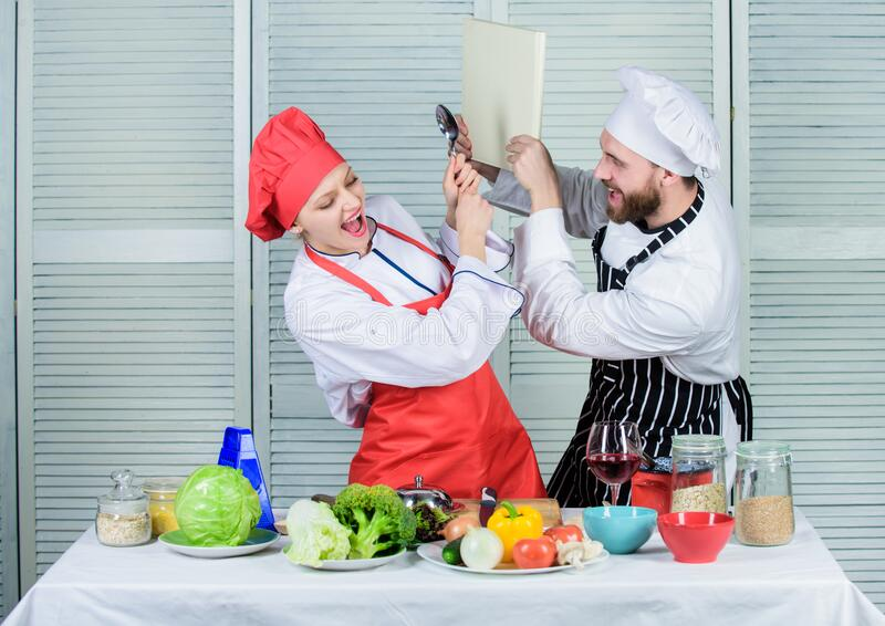 Couple in love cooking healthy recipe. Couple fight for book recipes. Improve cooking skill. Book recipes. Helpful stock images