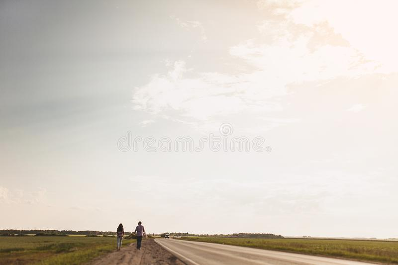 Couple in love is on a country road. The concept of hitchhiking. Rear view. Copy space for text.  royalty free stock image