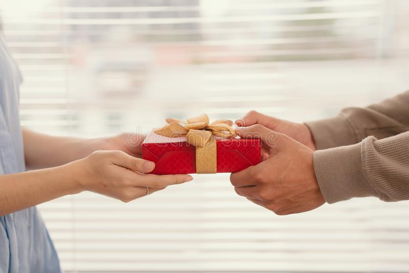 Couple in love. Man giving to his woman a gift box stock image