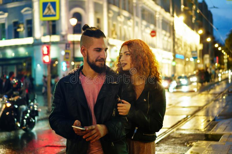 Couple in love on date. Boyfriend holds cellphone. She hugs him and smokes an electronic cigarette. They walk streets of night royalty free stock photos