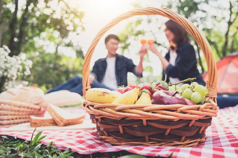 Couple in love drink a orange juice and fruits on summer picnic, leisure, holidays, eating, people and relaxation concept.  royalty free stock image