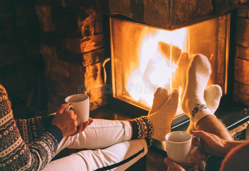 Couple in love drink a tea near fireplace. Cozy christmas home a stock images