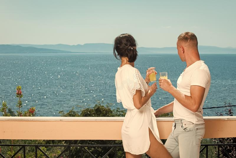 Couple in love drinking juice on balcony, nature and sea on background. Man and lady in bathrobe hold glass with drink. Vacation and relax concept. Couple royalty free stock images