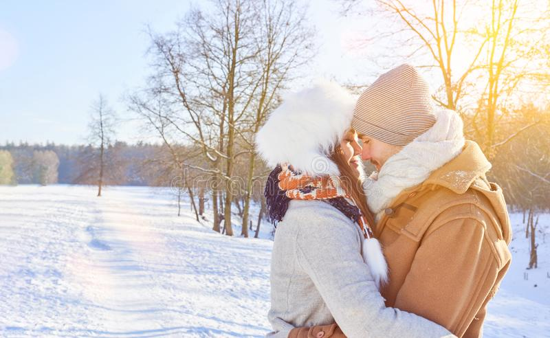 Couple in love embrace in winter. In the snow kissing stock images