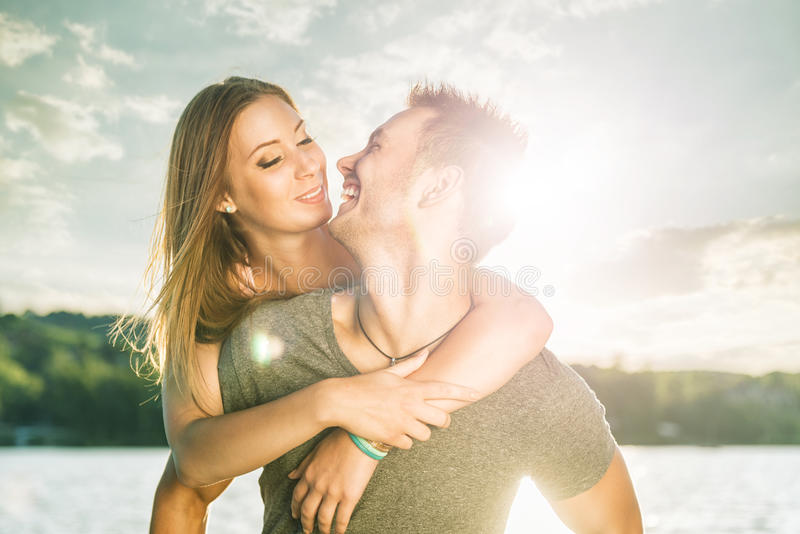Couple in love embracing at the lake, sun flare stock photography