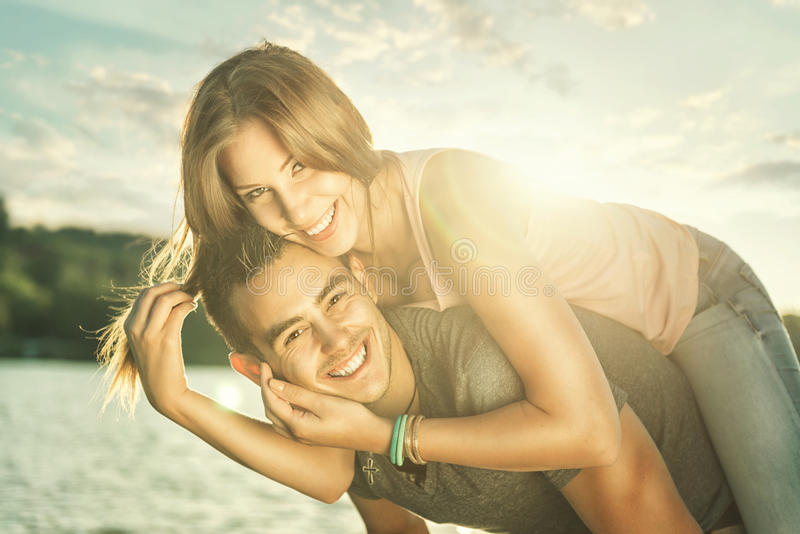 Couple in love embracing at the lake, sun flare stock photos