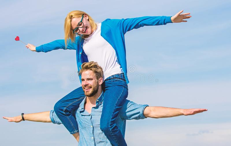 Couple in love enjoy feeling freedom outdoor sunny day. Couple happy date having fun together. Man carries girlfriend on. Shoulders, sky background. Lovers stock image