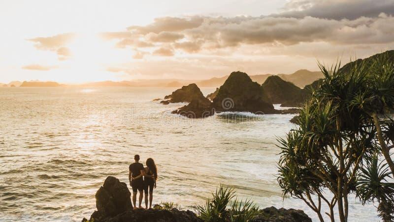 Couple in love enjoying sunset with amazing ocean and mountain view. Couple enjoying sunset with amazing ocean and mountain view. Travel concept, panoramic shot royalty free stock photo