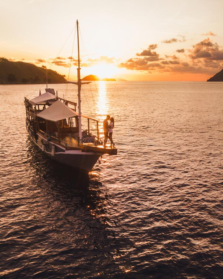 Couple in love enjoying sunset on yacht board stock images