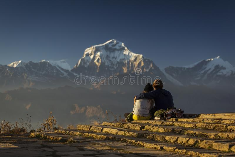 Couple in love enjoying view of Dhaulagiri from Poon Hill. Himalaya Mountains, Nepal. stock photography