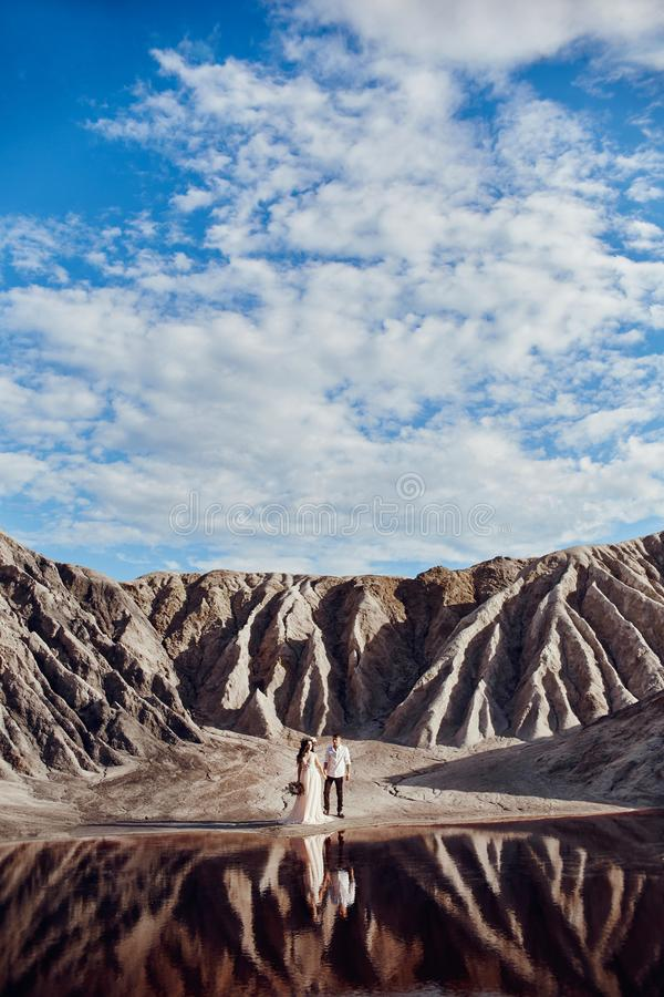 Couple love in fabulous mountains hugging near red lake, fabulous scenery. Lovers walk in mountains in summer stock photo
