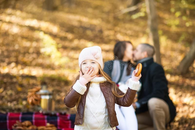 Couple in love in the fall at a picnic. A little girl with a bagel sends a kiss against the background of kissing parents in the f stock photo