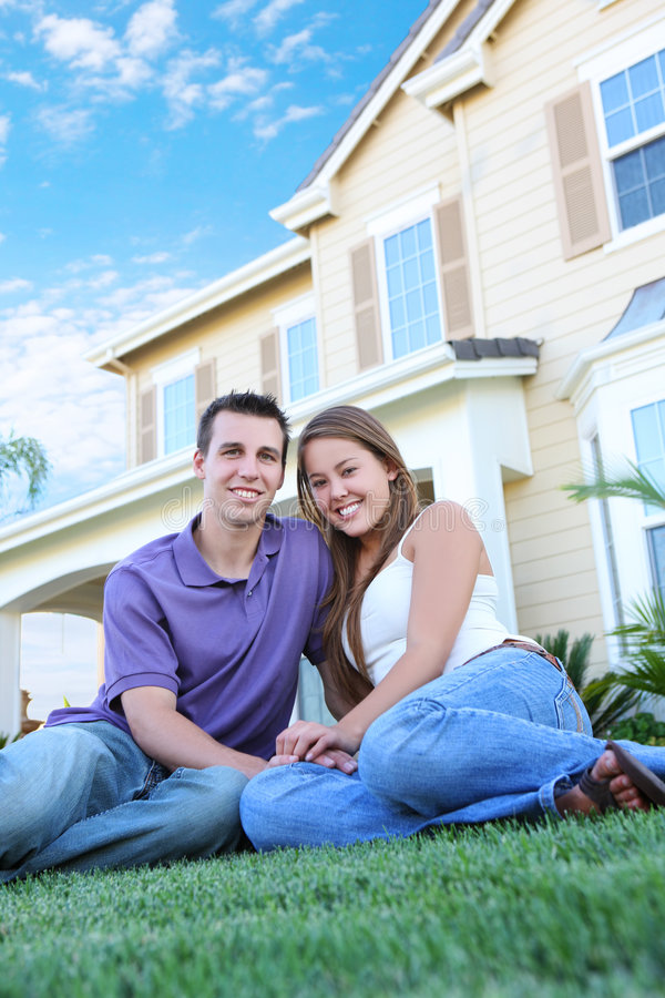 Couple in Love in Front of Home. A young man and woman couple in love in front of their new home
