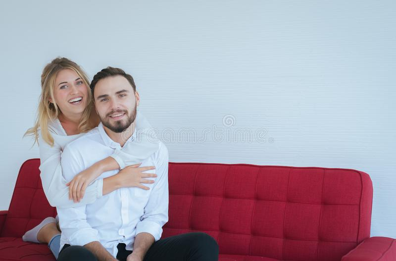 Couple in love girlfriend hugging her boyfriend on red sofa at home,Loving everything together,Happy and smiling stock photography