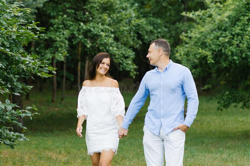 A couple in love, a guy and a girl holding hands, walking in the Park and smiling at each other royalty free stock photos