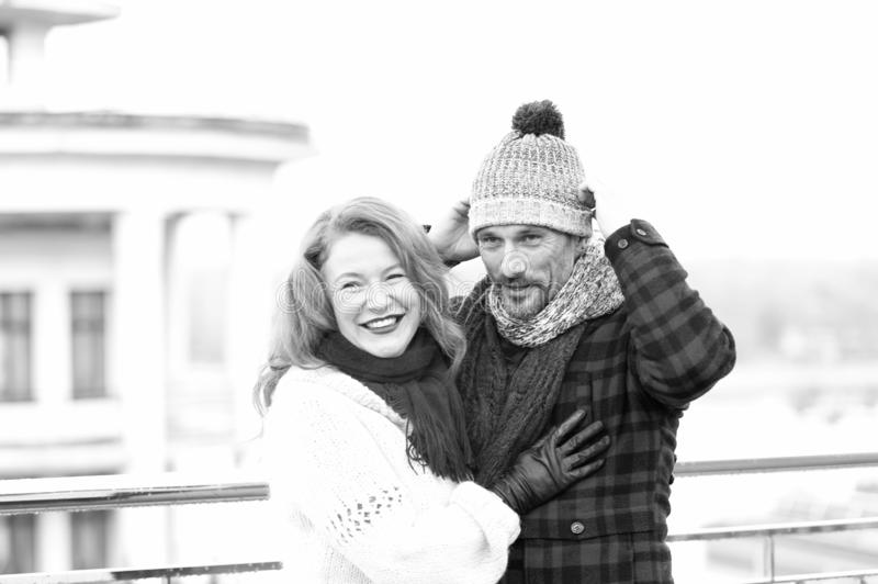 Couple in love. Happy woman hugs man. Guy dressed hat and smiling woman with scarf. Smiling couple royalty free stock images