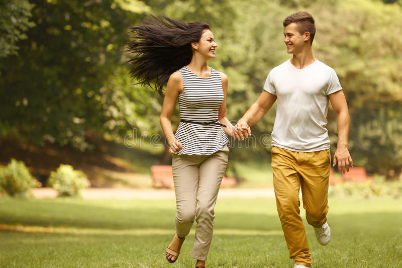 Couple in Love. Happy Couple Running in the park royalty free stock photo