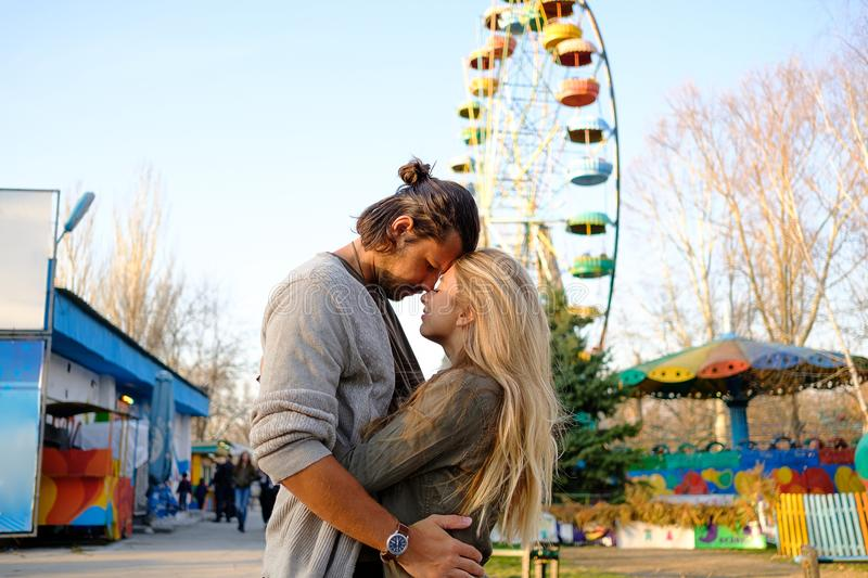 Couple in love. Happy smiling couple in love hug and kiss each other in the amusement park. Sunny warm spring evening royalty free stock photo