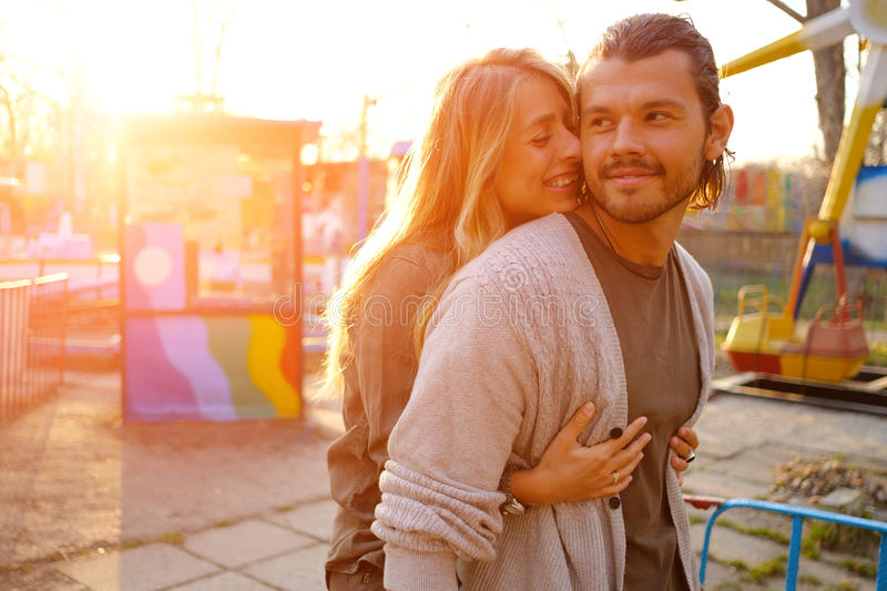Couple in love. Happy smiling couple in love hug and kiss each other in the amusement park. Sunny warm spring evening royalty free stock image