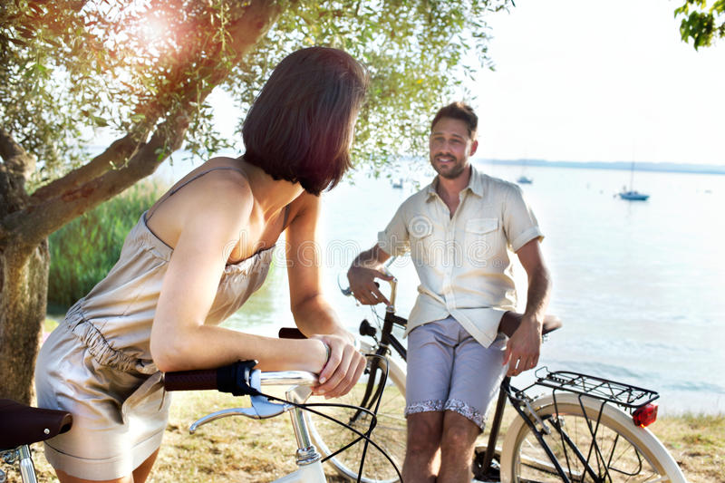 Couple in love having fun by bike on holiday to the lake royalty free stock image